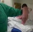 女婴刚降生 扶着助产士胳膊走路